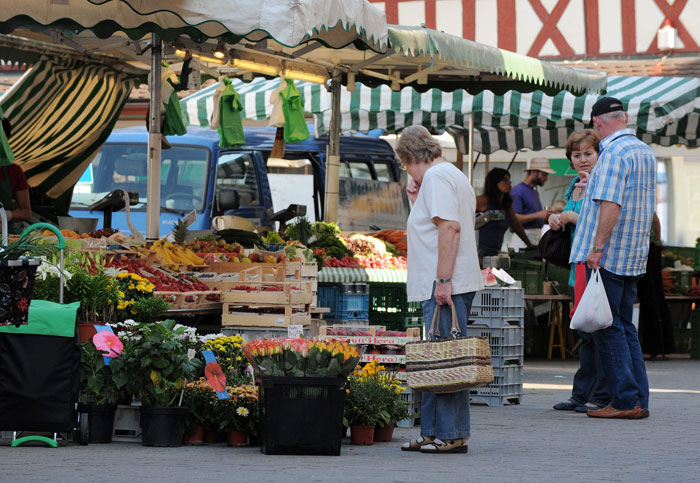 Kunden vor einem Marktstand mit Obst und Blumen