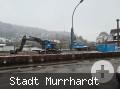 blauer Bagger steht auf dem Baustellengelände