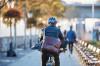 Ein Mann mit Tasche auf dem Fahrrad unterwegs zur Arbeit