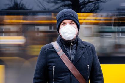 Mann mit FFP2 Maske wegen Corona Maskenpflicht im öffentlichen Nahverkehr vor Haltestelle